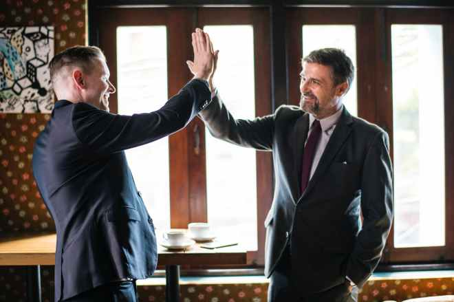 two men standing while doing high five
