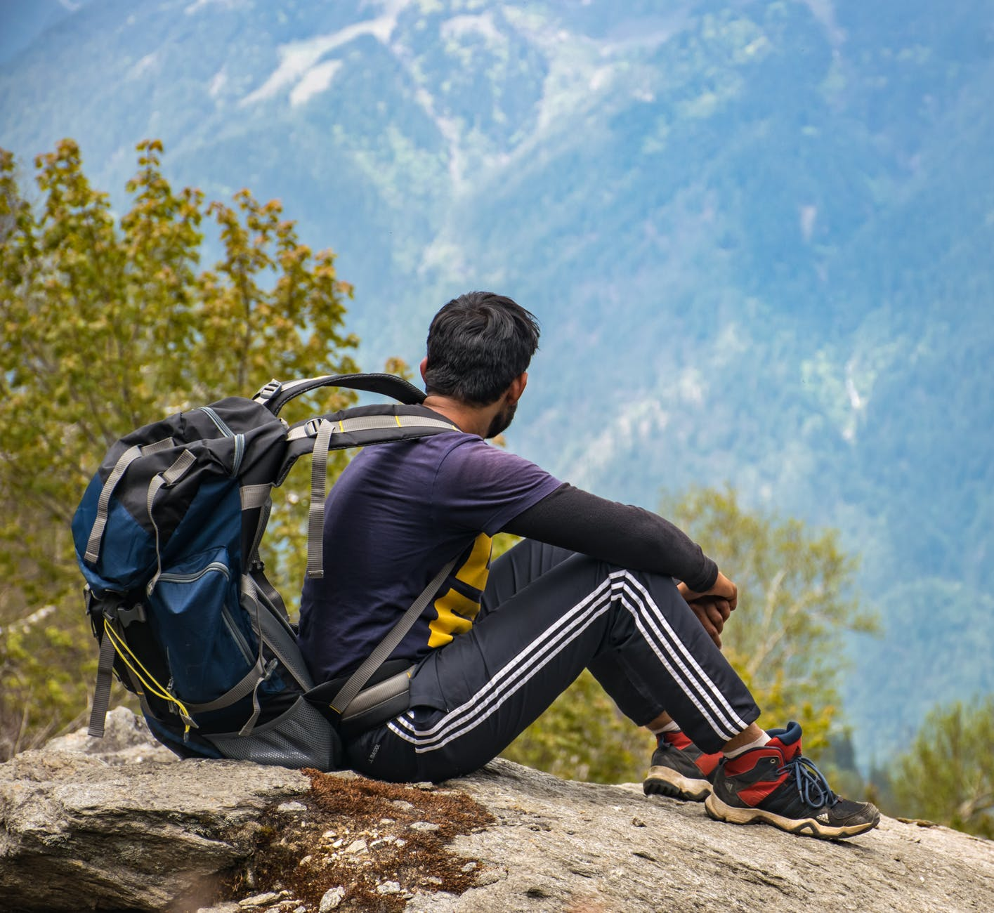 man in purple t shirt with blue backpack sitting on gray boulder